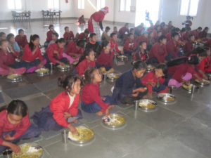 Children eating while watching educational TV at FFP facility
