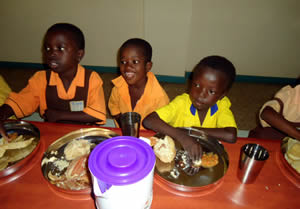 Children in Otinibi, Ghana enjoying a meal the FFP facility