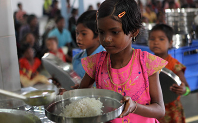 A girl eats food from The Prem Rawat Foundation's Food for People program